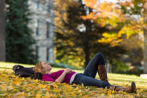 Student lying on Bascom Hill in fall